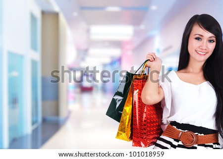 Beautiful shopping woman with shopping bags in a mall