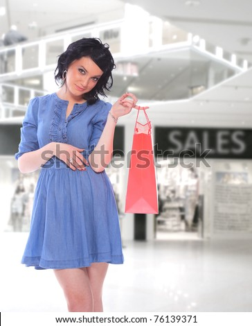Beautiful shopping women with colorful bags at the mall