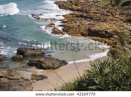 Beautiful shoreline with red rocks and green water