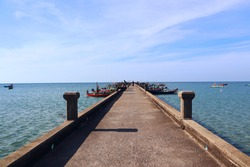 Beautiful shot of a long jetty. jetty over the beautiful sea with blue sky. Tourism and Vacations Concept. Fishing port. Chao Lao Beach. Chanthaburi Province, Thailand.