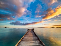 Beautiful shot of a long jetty/pier at sunset. Minimal image with jetty in the center stretching to the ocean. Warm sunset tones of orange, yellow, pink, blue and purple. Smooth water and reflection