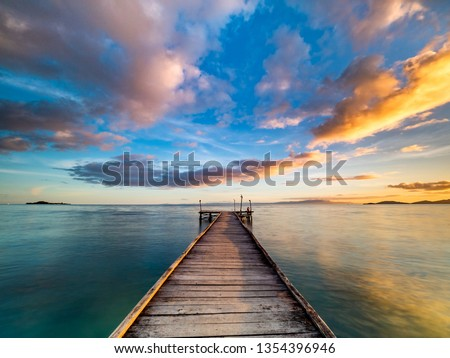 Photo of  Beautiful shot of a long jetty/pier at sunset. Minimal image with jetty in the center stretching to the ocean. Warm sunset tones of orange, yellow, pink, blue and purple. Smooth water and reflection