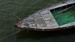 Beautiful shot of boat in the river Ganges with selective focus. White and green boat is parked for riding and waiting for the people with copy space. Boating in river Ganges in Varanasi.