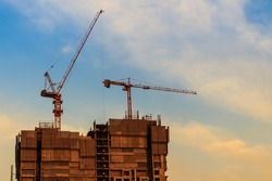 Beautiful silhouette of construction tower cranes with sunset sky background. Silhouette of the building construction with the tower cranes on top under the dramatic sky background.