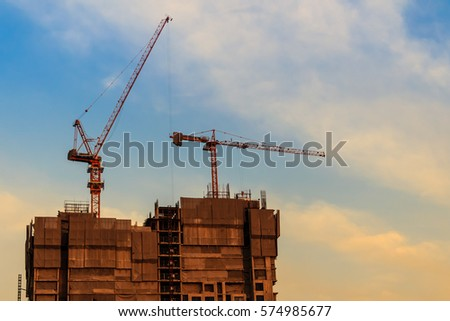 Beautiful silhouette of construction tower cranes with sunset sky background. Silhouette of the building construction with the tower cranes on top under the dramatic sky background. #574985677