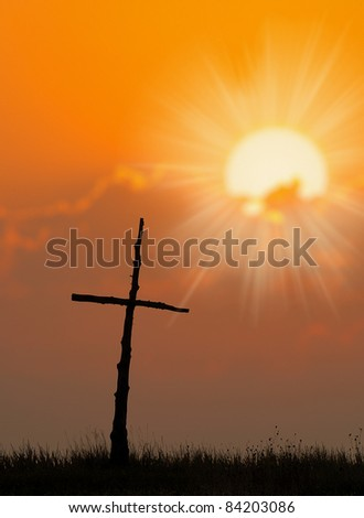 Beautiful silhouette of Cross and sunrise over a meadow on a cool fall morning.