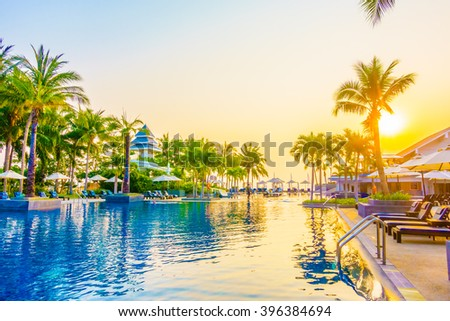 Beautiful Silhouette palm tree with umbrella and chair around luxury swimming pool in hotel resort at sunset time - Vintage Filter and Color boost Up Processing #396384694