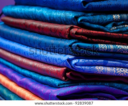 Beautiful silk of different colors and ornament Indian fabric laying in pile