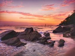 Beautiful silky smooth water with vivid sunset color over the stony seashore at Rasa Ria beach, Tuaran, Sabah. Malaysia, Borneo.