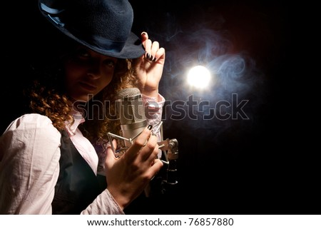 Beautiful singer in hat with microphone on the black background
