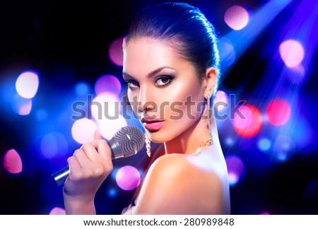Beautiful Singing Girl. Beauty Glamor fashion Woman with Microphone over Blinking bokeh night background. Glamour Model Singer. Karaoke song. Karaoke party