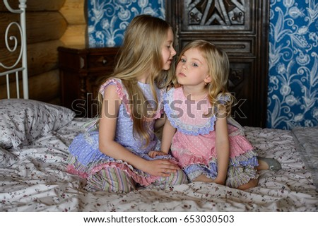 Beautiful sisters in sleepwear, play on bed #653030503