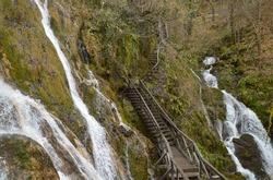 Beautiful Skakavac waterfall with wooden boardwalk between cascades,
