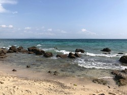 Beautiful sky and rocky coast on Koh Mannork Island, Rayong, Thailand. A photograph of the sea surface and rocky shore. Sea wave splashing on stone at sea shore. Beautiful view of the Indian Ocean.