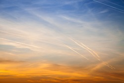 Beautiful sky at sunset, streaked airplane traces. Contrast between warm and cold colors Concept for environmental protection