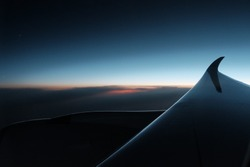 Beautiful sky clouds seeing through the Airbus A350 windows. Sunset aerial view through airplane window over wings. Flying at sunset and looking out of the window and enjoying the panoramic view.