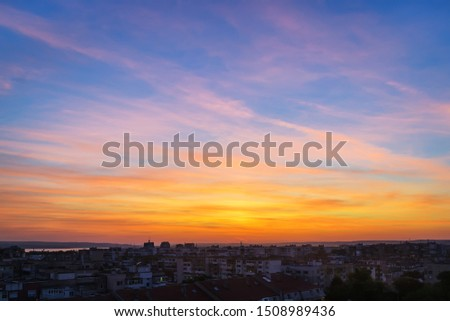 Beautiful skyscape at the sunset time over a small city. Vivid sky of golden and orange colors during sundown. Evening landscape. Beauty in nature. #1508989436