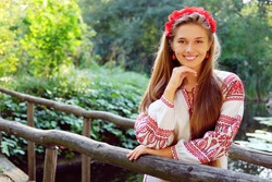 Beautiful slavonic girl with long blond hair and blue eyes with flower crown in white and red embroidered costume waiting at the bridge.Traditional clothes of Ukrainian region.
