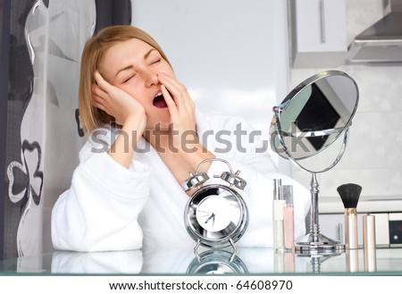 beautiful sleepy woman applying makeup at home