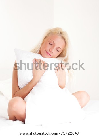 beautiful sleepy young blond woman with a pillow on the bed at home