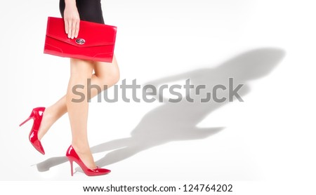 Beautiful slender womanish feet are in red shoes,  shade from a model in complete growth