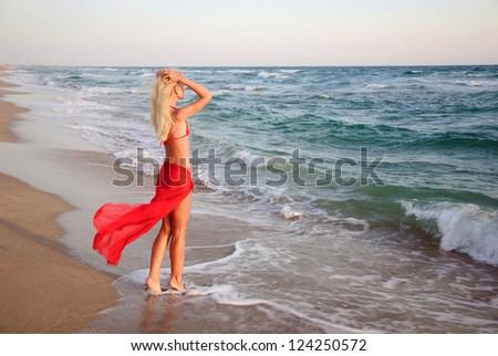 beautiful slender young blonde woman in red skirt and bikini on the sea beach - romantic waiting concept