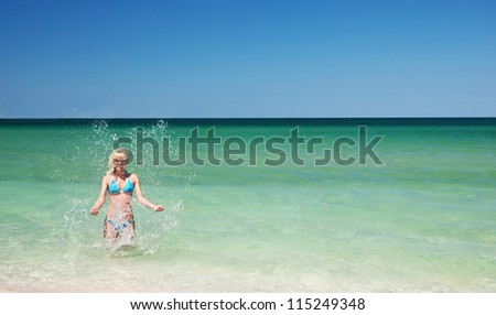 beautiful slender young woman on the sea beach in summer bright day