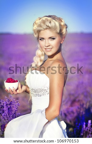 beautiful slim bride in luxurious wedding dress in purple lavender flowers. Fashion romantic stylish happy woman with blond hair. Smiling girl in sunset over summer lavenda waiting for groom -Provence