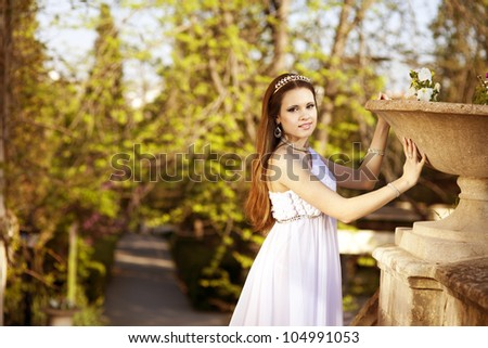 beautiful slim bride in luxury dress in park on sunset near blossom flowers in wedding day. young woman in Greek goddess style with diamond tiara and jewelery outdoor. romantic girl with glossy hair. - stock photo