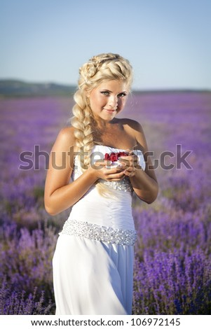 beautiful slim bride in luxury wedding dress in purple lavender flowers. Fashion romantic happy woman with blond hair. Smiling girl resting on sunset in summer lavender field waiting for groom.Series