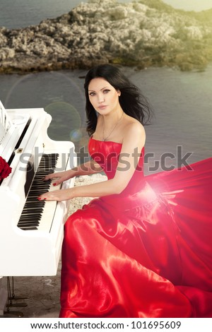 beautiful slim bride in red wedding dress playing grand piano on sunset beach. Fashion romantic stylish arabian young girl musician with long glossy healthy hair. Spring - summer