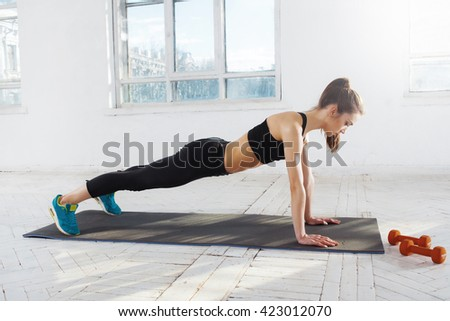 Photo of  Beautiful slim brunette  doing some push ups a the gym