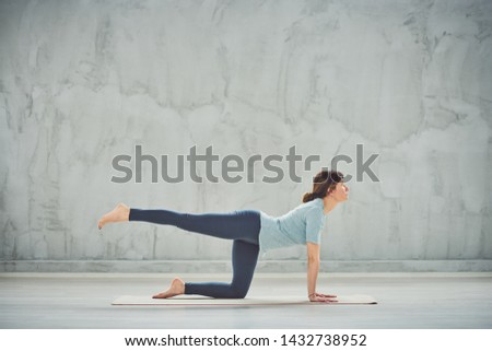 Beautiful slim Caucasain brunette kneeling on the mat barefoot and doing One Legged Table yoga pose.