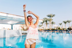 Beautiful slim girl in fringe shirt and white panties having fun near the warm blue water with palm trees on background. Cute young woman laughing and dancing at the pool on exotic resort in weekend