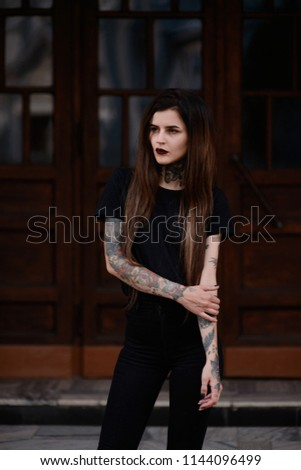Beautiful slim girl with black lips tattoos and piercing wearing casual  black clothes, standing against the wooden doors. Tattooed young female model in black #1144096499