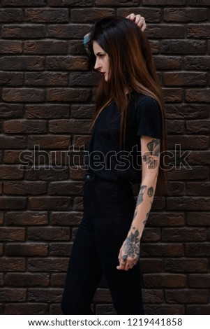 Beautiful slim girl with tattoos and piercing, wearing casual clothes, black t shirt and jeans standing against the stone wall or brick fence. Tattooed young female model. Alternative lifestyle #1219441858