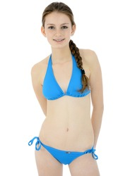 Beautiful slim teenager wearing a blue bikini in studio isolated on white
