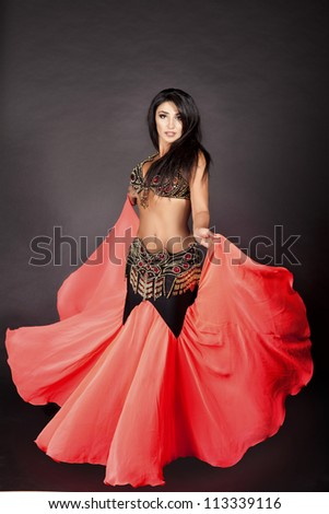 beautiful slim woman belly dancer. sexy arabian oriental professional artist in carnival shining costume with long healthy glossy hair. exotic star of bellydance. dancing girl brunette