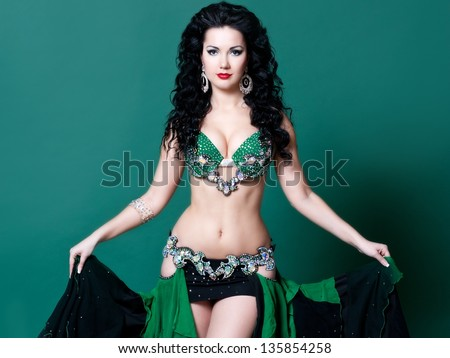 beautiful slim woman belly dancer sexy arabian turkish oriental professional artist in carnival shining costume with long healthy glossy hair. exotic star of bellydance