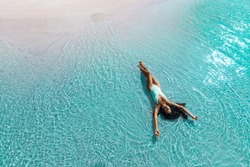 Beautiful slim woman lying on the beach in white swimsuit. Aqua Menthe trendy color of the new year 2020. Leisure island vacations concept.