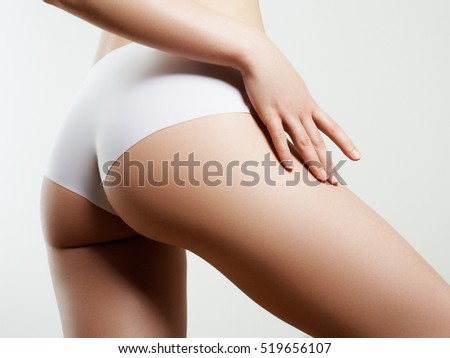 Beautiful slim woman's body. Perfect slim toned young body of the girl. Fitness or plastic surgery and aesthetic cosmetology. Taut elastic ass. Firm buttocks