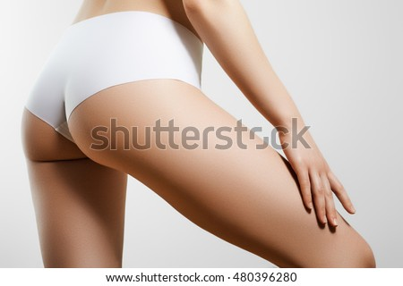 Beautiful slim woman's body. Perfect slim toned young body of the young girl. Fitness or plastic surgery and aesthetic cosmetology. Perfect buttocks