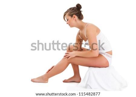 Beautiful, slim woman sitting on white background