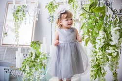 beautiful small girl in silver dress staying in nice luxury interior