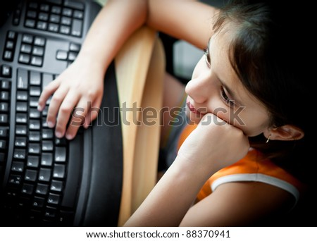Beautiful small girl working on a personal computer at home