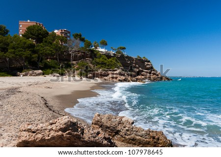 Beautiful small sandy beach on the coast of Costa Brava, Spain. With cliff, house and tree