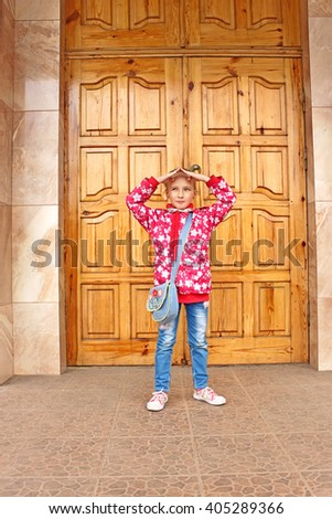 Beautiful small schoolgirl standing and posing before big wooden door