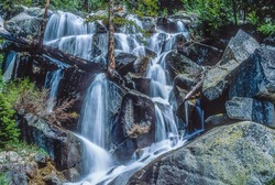 Beautiful small waterfall cascading over rocks in Sierra Nevada, California