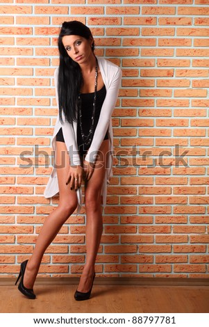 beautiful smart woman with black hair stands near brick wall; full body
