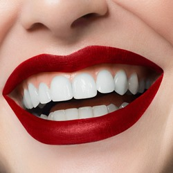 Beautiful smile with whitening teeth. Dental photo. Macro closeup of perfect female lipscare. Perfect red lip makeup. Perfect clean skin, light fresh lip make-up. Isolated. Good sunny mood